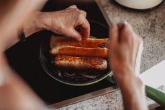 Den gamla kvinnan lagar mat någon bratwurst royaltyfria bilder