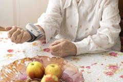 Den gamla kvinnan mäter arteriellt tryck, medan sitta i vardagsrummet på tabellen Arkivfoto