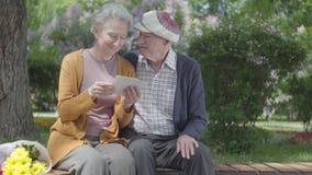 Den gamla kvinnan med buketten av gula blommor sitter i b?nken i gr?nt h?rligt parkerar med en gamal man och uppvisning honom stock video