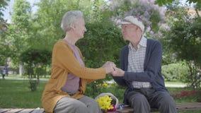 Den gamla kvinnan med buketten av gula blommor som sitter med en gamal man och rymmer h?nder i b?nken i, parkerar anbud arkivfilmer
