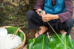 Den gamla kvinnan räcker att förbereda sig att göra Chung Cake, den vietnamesiska mån- Tet för det nya året maten Royaltyfri Bild