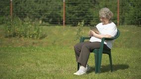 Den gamla kvinnan rymmer en silverdatorminnestavla utomhus arkivfilmer