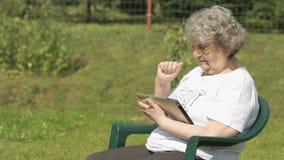 Den gamla kvinnan rymmer en silverdatorminnestavla utomhus lager videofilmer