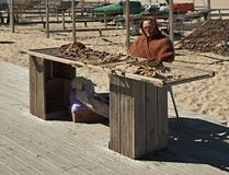 Den gamla kvinnan säljer den torkade fisken på stranden av Nazare, Centro - Portugal arkivbilder