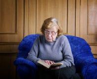 Den gamla kvinnan sitter i en fåtölj Arkivbild