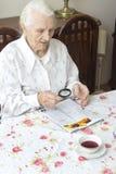 Den gamla kvinnan sitter på en tabell med en tidning Arkivfoto