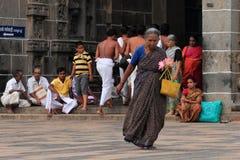 Den gamla kvinnan skriver in den Nataraja templet Arkivbilder