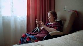 Den gamla kvinnan skriver ett meddelande och blickar på fotona på hennes smartphone Mormor med djupa skrynklor inomhus lycklig pe lager videofilmer