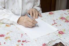 Den gamla kvinnan skriver handskriven will Arkivfoto