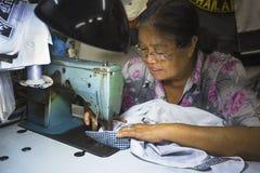 Den gamla kvinnan syr på symaskinen i gatan Fotografering för Bildbyråer