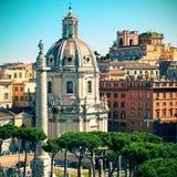 Den gamla kyrkan och forntida Trajans kolonn i Rome Arkivbilder