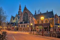 Den gamla kyrkliga Ouden Kerk i den Amsterdam staden på natten, Nederländerna fotografering för bildbyråer