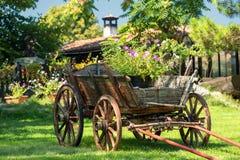 Den gamla lantliga trälantliga vagnen med sommar blommar Arkivbild