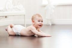 Den gamla lyckliga sju månaden behandla som ett barn flickakrypning på ett ädelträgolv royaltyfri fotografi