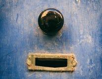 Den gamla mässingspostbrevlådan och svartknoppen på en blått målade ytterdörren arkivbilder