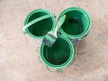 Den gamla målarfärgborsten vilar överst av den gröna målarfärghinken Royaltyfri Fotografi