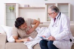 Den gamla manliga doktorn som bes?ker den unga manliga patienten arkivbilder