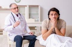 Den gamla manliga doktorn som bes?ker den unga manliga patienten arkivbild