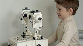 Den gamla manliga doktorn undersöker ögon av pojken till och med den skurna upp lampan Royaltyfria Bilder