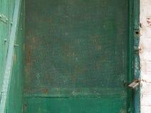 Den gamla metall- och trädörren med ett rostigt lås i en tillfällig källare grävde i jordningen fotografering för bildbyråer