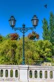 Den gamla metalliska gatalampan i ett offentligt parkerar royaltyfri foto