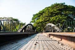 Den gamla metalljärnvägsbron som som leder till trädtunnelen Arkivfoto