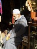Den gamla moroccan säljaren i hans shoppar Arkivbild