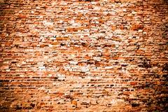 Den gamla och red ut grungy röda orange tegelstenväggen som täckas delvis av överskott cement och grå färger, målar som texturbak royaltyfri fotografi
