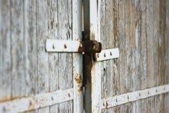 Den gamla porten med rostigt låser och målad vit arkivbild