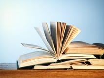 Den gamla öppna romanen bokar på en trätabell Royaltyfri Bild