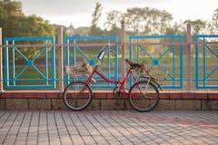 Den gamla röda cykeln med korgar står på staketet på solnedgången arkivfoto