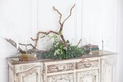 Den gamla rokokobyrån dekoreras med böcker, stearinljus, drivved och växter mot väggen med stuckaturen royaltyfri fotografi