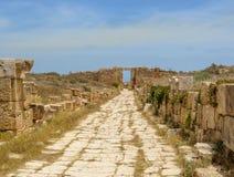 Den gamla romerska gatan som leder till nyckeln på den forntida romaren, fördärvar av Leptis Magna i Libyen Arkivfoto