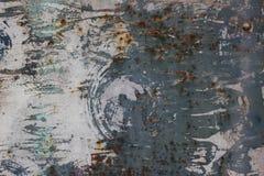 Den gamla rostiga metalldörren med sprickor, rost och lossar smutsig textur för stycken Arkivfoto