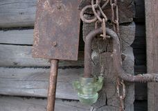Den gamla rostiga metallkedjan, skyffel, den glass lyktan på trät loggar lodisar Royaltyfri Fotografi