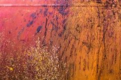 Den gamla rostiga orange röda järnmetallväggen med färg plaskar Arkivbild