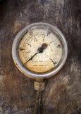 Den gamla rostiga runda industriella tryckmätaren med nummer rundar visartavlan Arkivbild