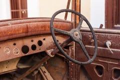 Den gamla rostiga styrningen för den motoriska bilen rullar in en restgård royaltyfri bild