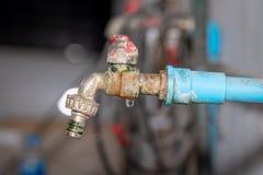Den gamla rostiga vattenkranen med att läcka för vatten royaltyfria foton