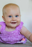 Den gamla söta 6 månaden behandla som ett barn flickan som ler på vit Arkivfoton