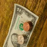 Den gamla sedeln av två US dollar och skrapade cent USA ligger på a Fotografering för Bildbyråer