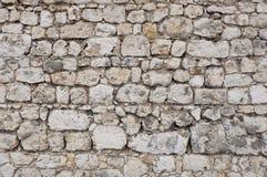 Den gamla slott- eller fästningstenväggen som göras av vit och grå färger, stenar kvarter arkivbild