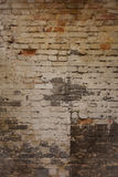Den gamla smutsiga red ut tegelstenväggen med kritamålarfärg återstår Arkivfoton