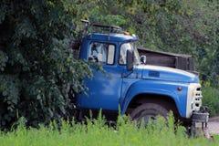 Den gamla sovjetiska lastbilen med en blå taxi tog fristaden i skuggan av grön lövverk royaltyfri foto