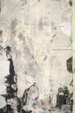 Den gamla spruckna anslagstavlaväggen med vilar av papper, vit grung Royaltyfria Foton