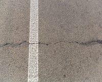 Den gamla spruckna asfaltvägen Vit teckning på vägen Reparationen krävs kopiera avstånd Arkivfoto