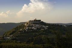 Den gamla staden av Motovun i Istria stiger upp på kullen i solnedgång för sen sommar med vingårdar i förgrund arkivbilder
