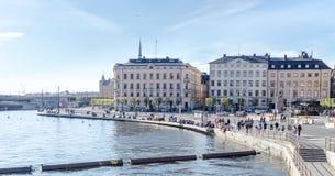 Den gamla staden i Stockholm en solig och tidig vårdag och peple sitter på landningen och kopplar av i det varma vädret Arkivfoton