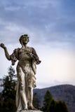 Den gamla statyn som ser himlen i ett offentligt, parkerar Arkivfoton