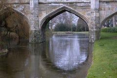 Den gamla stenbron välva sig med vallgraven i England Arkivbild